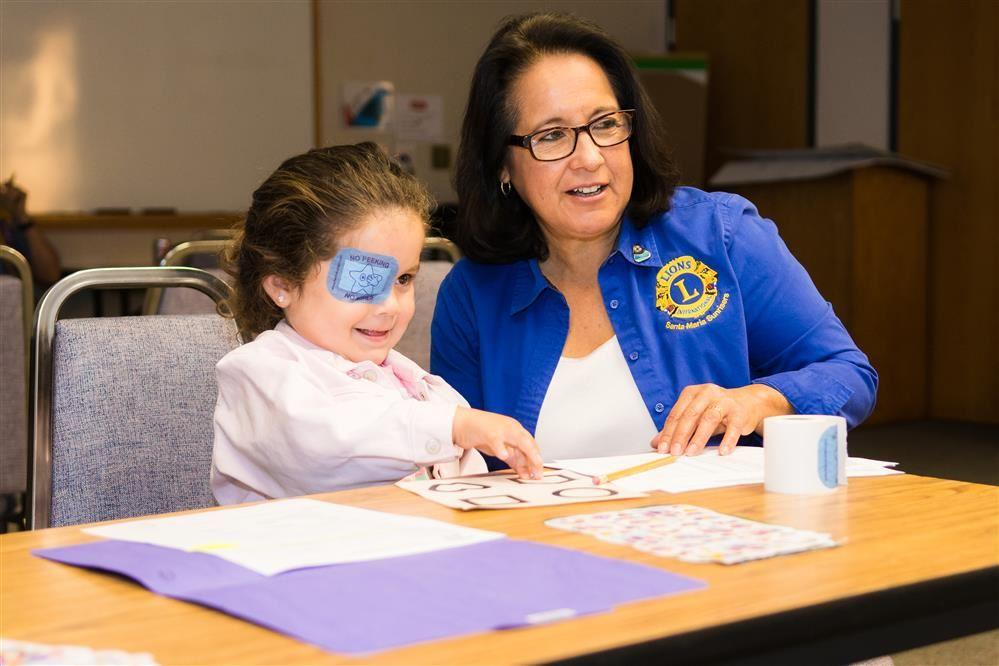 Adult helping child with eye screening