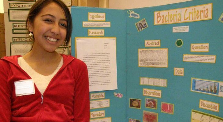 Girl smiling in front of her science project.
